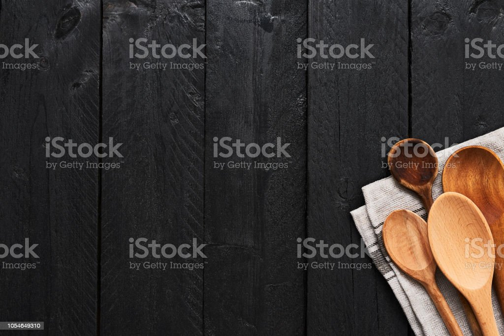 Wooden spoons and dishtowel on black wooden background with copy...