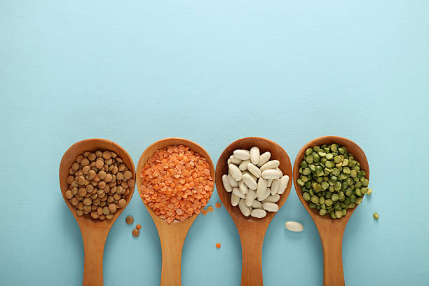 wooden spoons and various legumes stock photo