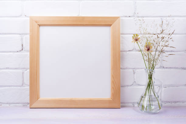 Wooden square frame mockup with grass in the glass jug stock photo