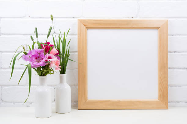 Wooden square frame mockup with pink godetia flowers stock photo