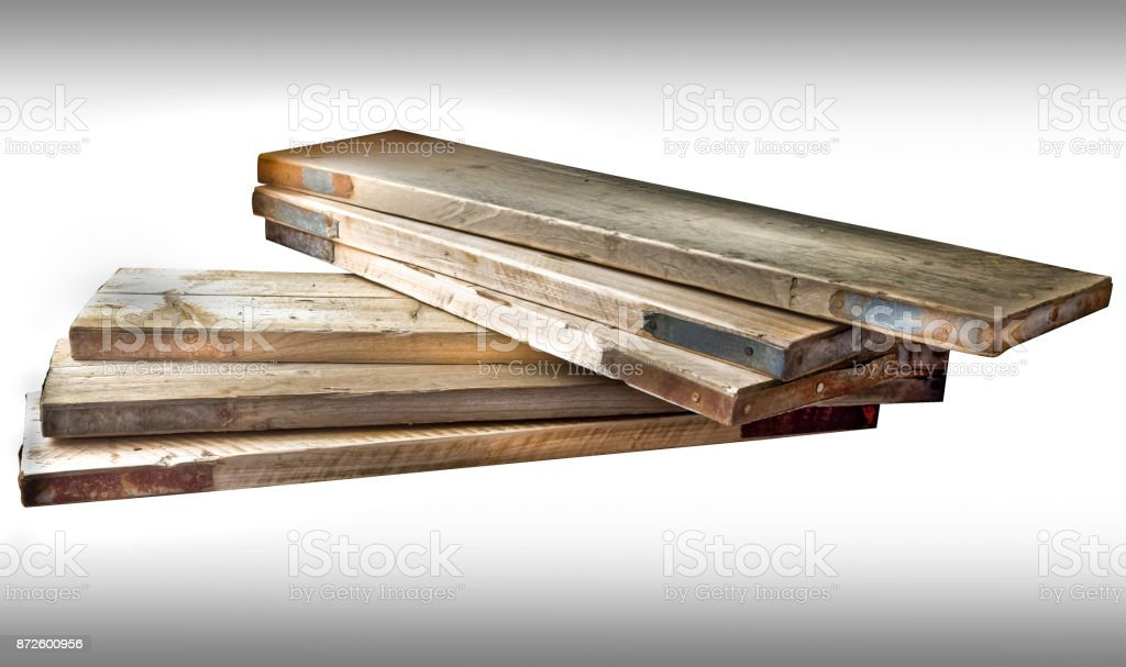 Wooden stack of scaffolding battens, planks or boards with protective metal end grain plates against white background. stock photo