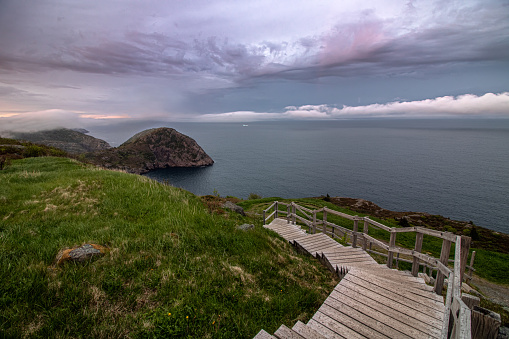 A wooden staircase leading down to a dramatic coastal seascape with ominous clouds and fog rolling in.