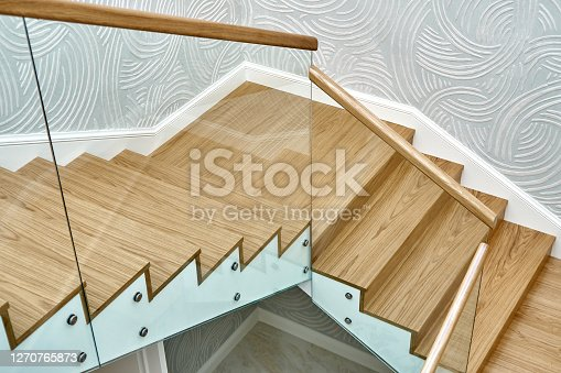 Wooden staircase with glass railings and wooden handrail. View from above