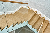 istock Wooden staircase with glass railings and wooden handrail 1270765873