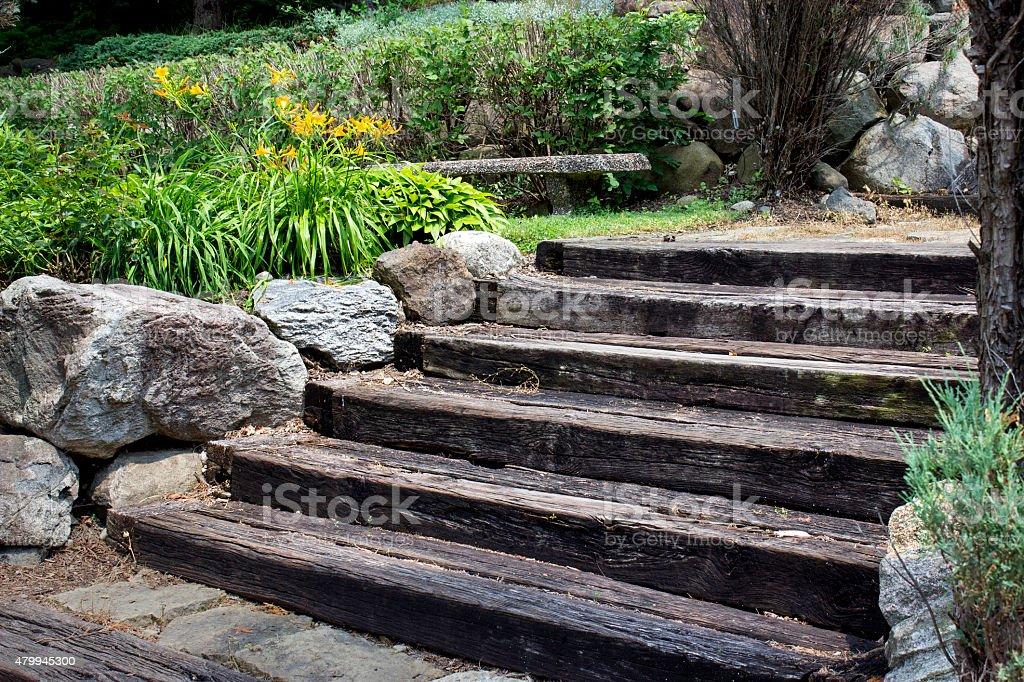 wooden stairs with boulders and golden flowers stock photo
