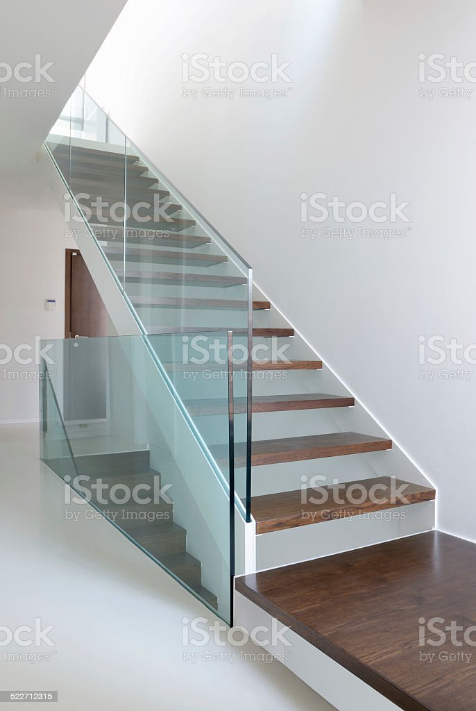 wooden stairs with glass balustrade stock photo