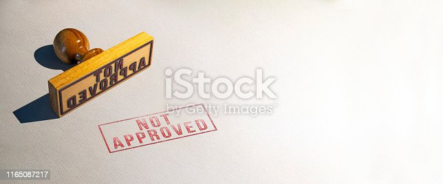 light color wooden real stamp, stamped not approved text on patterned white real paper with copy space.