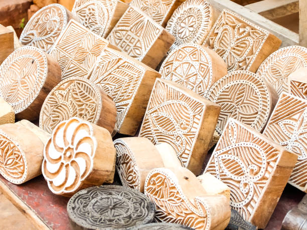 Wooden stamps printing blocks hand carved by artisans on the street market in Jaisalmer, India. Wooden stamps printing blocks hand carved by artisans on the street market in Jaisalmer, India. Henna stamps for decorating the body or clothes. carving craft product stock pictures, royalty-free photos & images