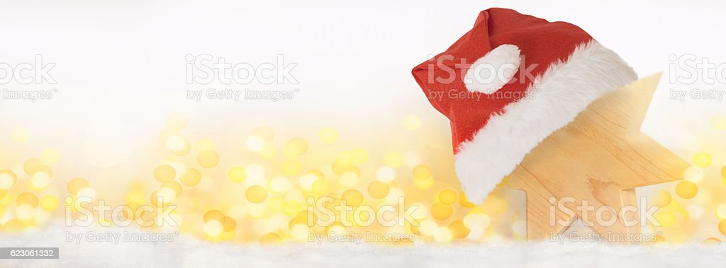 Wooden star with Christmas hat in snow stock photo