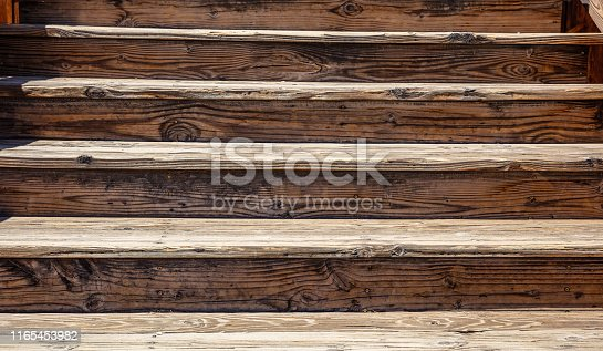 Wooden stairs old, vintage going up, full texture background. Sunny spring day