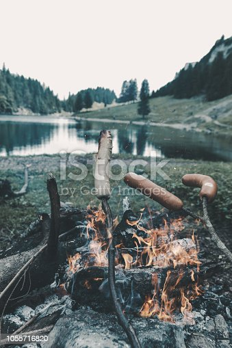 istock wooden sticks grilling barbecue sausages on fireplace in front of mountain lake 1055716820