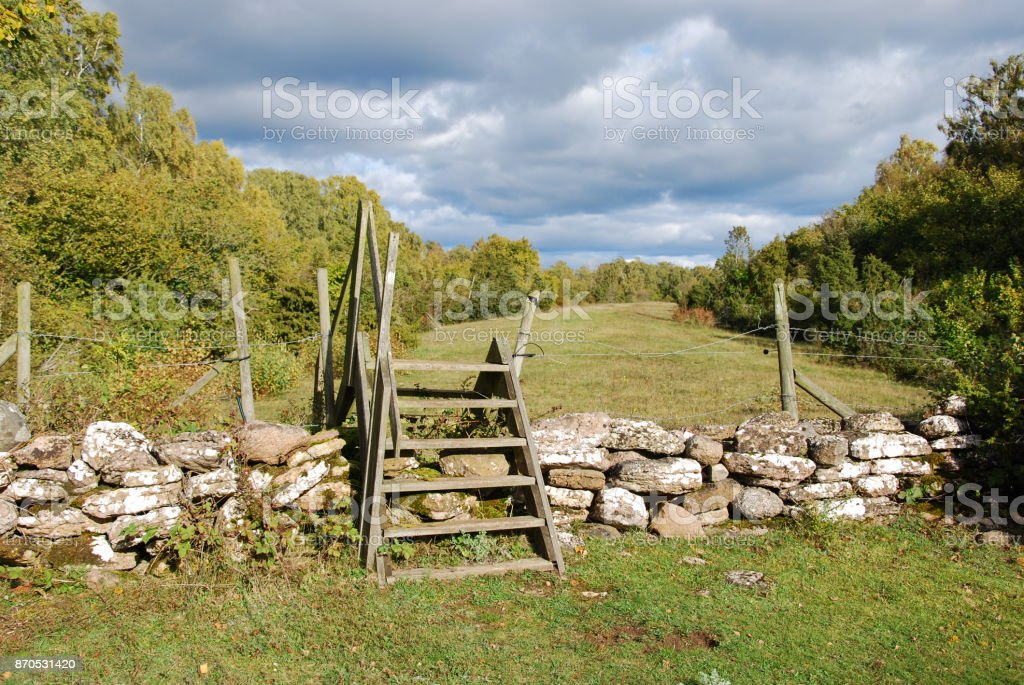 Wooden stile by a stone wall stock photo