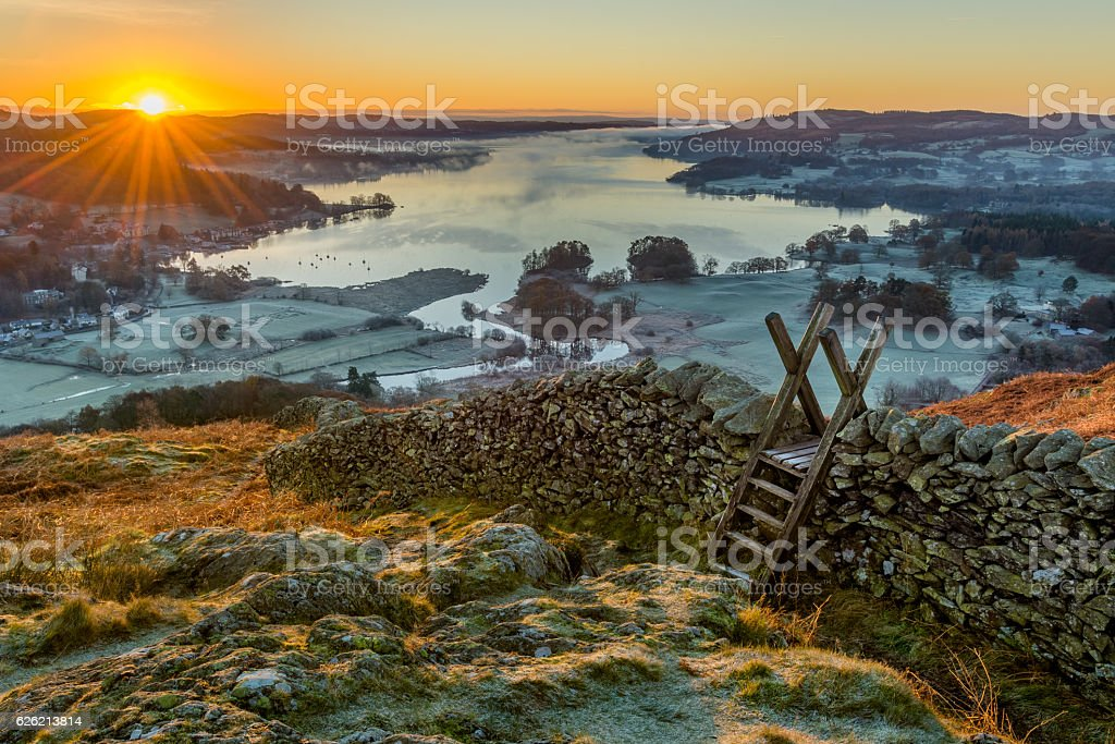 Wooden stile over stone wall with beautiful sunrise. stock photo