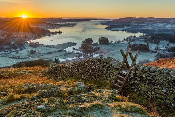 wooden stile over stone wall with beautiful sunrise. - cumbria stock photos and pictures