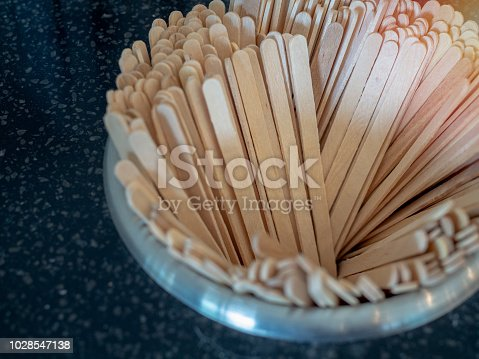 Wooden stir sticks in stainless pit on coffee bar in cafe.
