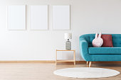 Mockup of white posters and lamp on wooden stool in child's room with blue sofa and white carpet