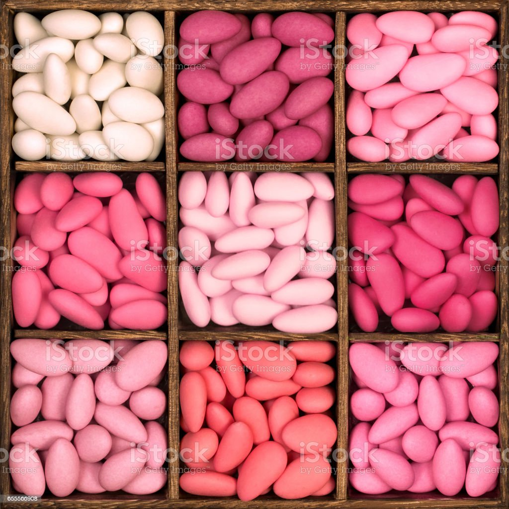 Wooden storage box filled with pink sugared almonds. - foto stock
