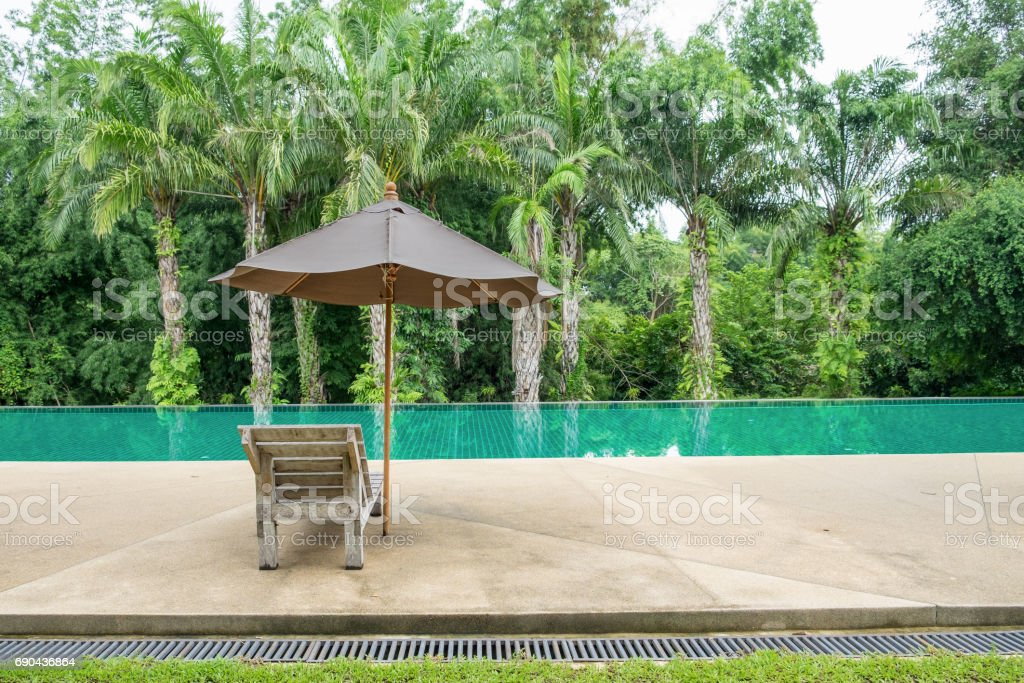 Wooden sunbed with umbrella on modern swimming pool stock photo