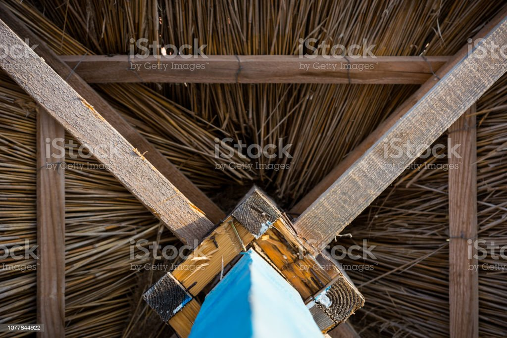 Wooden sunshade, straw umbrella with a blue foot, view from below – zdjęcie