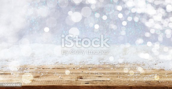 istock Wooden surface Christmas snowy background 1008906482