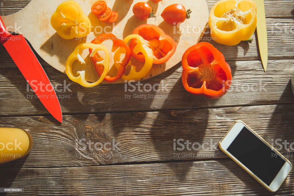 Wooden surface with sliced vegies and cellphone stock photo