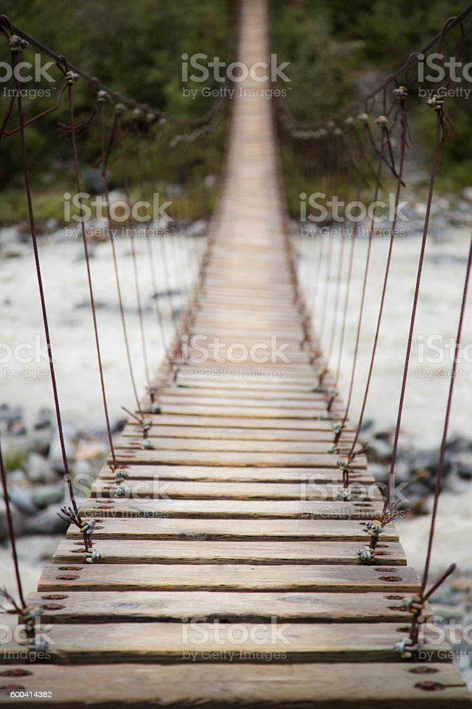 Wooden Suspension Bridge stretching across a flowing river in Al stock photo