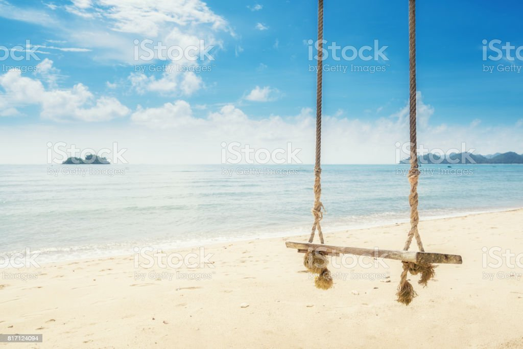 Wooden swing chair hanging on tree near beach at island in Phuket, Thailand. Summer Vacation Travel and Holiday concept. stock photo