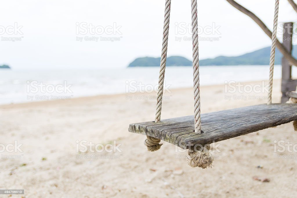 Wooden swing chair near the beach stock photo