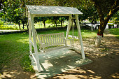 A wooden swing chairs around a park unique photo