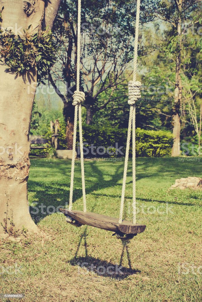 wooden swing in the garden vintage tone stock photo