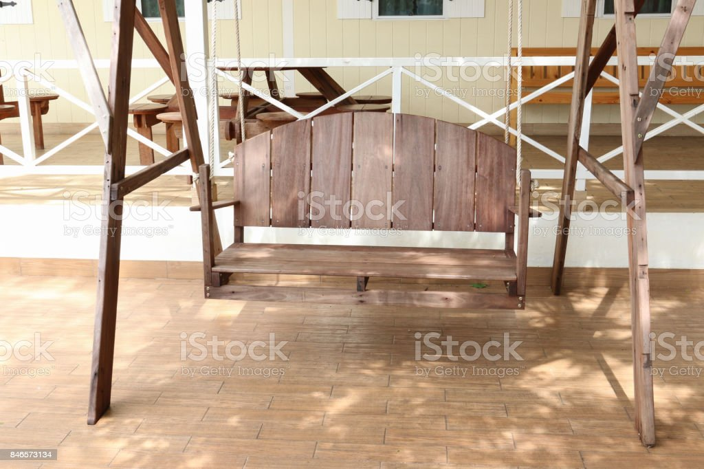 wooden swing with backrest on patio stock photo