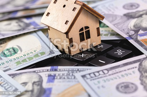 istock wooden symbol house with money, dollars on the calculator 1167627156