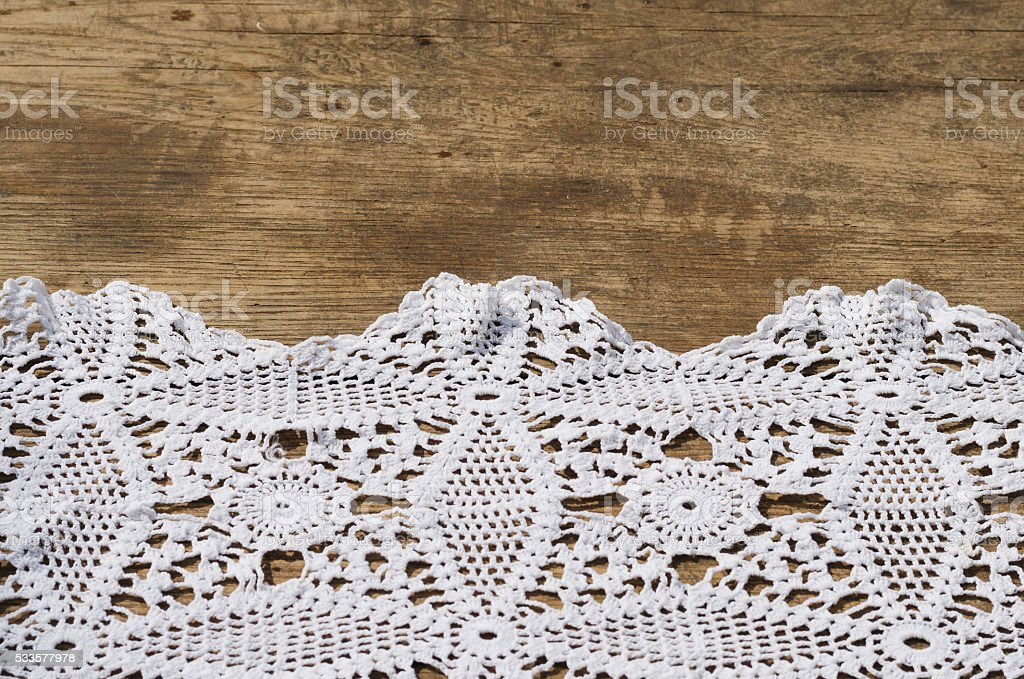 Wooden table and a white crocheted napkin stock photo