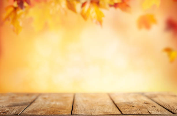 wooden table and blurred autumn background. autumn concept with red-yellow leaves background. - autumn foto e immagini stock