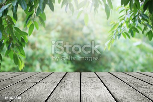 Wooden table and blurred leaf nature garden background.