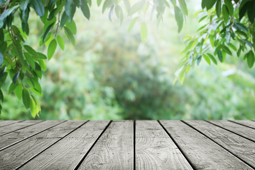 Wooden table and blurred green leaf nature in garden background.