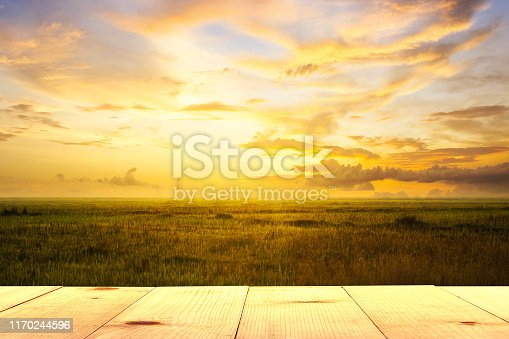wooden table and empty lawn at sunset