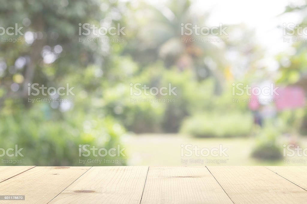wooden table and garden blurry background stock photo