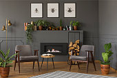 Wooden table between grey armchairs in retro flat interior with fireplace under posters. Real photo