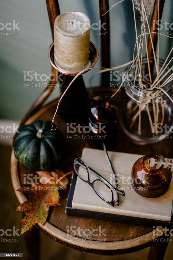 A wooden table decorated with an autumn theme featuring an aromatic...