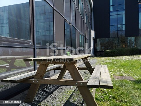 647209792 istock photo Wooden table for eating outside the company building 1154044050