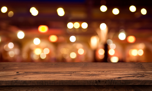 498688230 istock photo Wooden table for product display on abstract restaurant lights background 1002098742