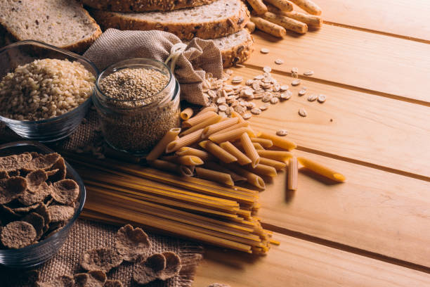 Wooden table full of fiber-rich wholegrain foods, perfect for a balanced diet Wooden table full of fiber-rich whole foods, perfect for a balanced diet rice cereal plant stock pictures, royalty-free photos & images