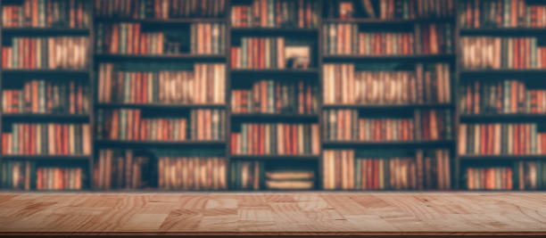 holztisch im unscharfen bild viele alte bücher im bücherregal in bibliothek - offene regale stock-fotos und bilder