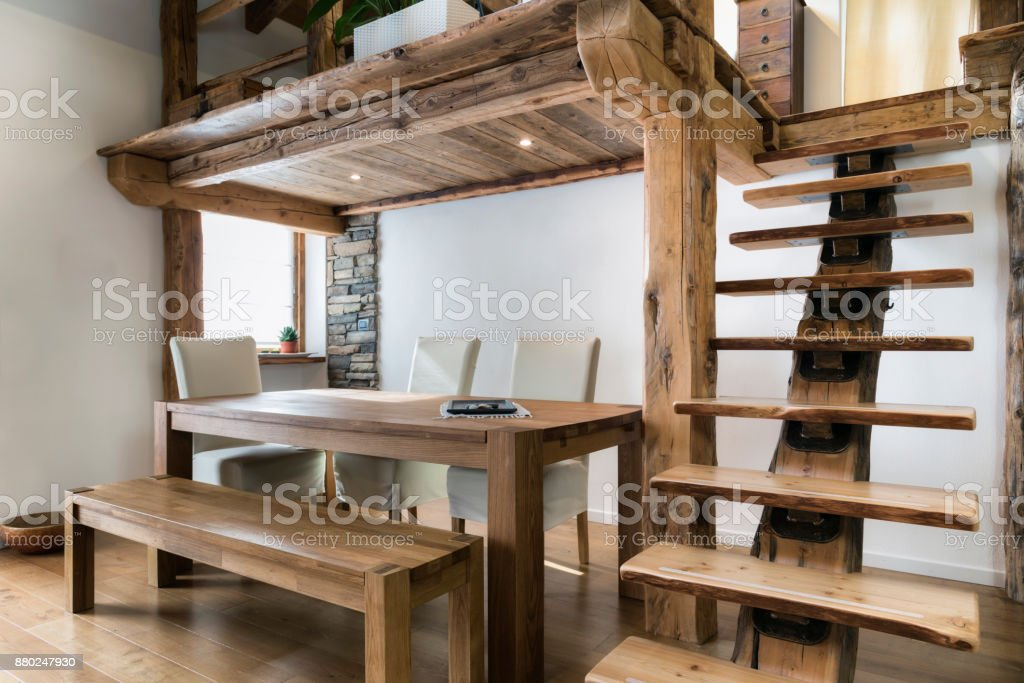 wooden table in dining room under mezzanine stock photo