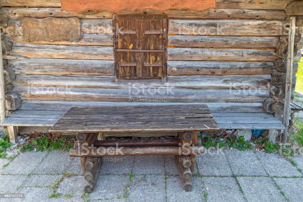 Wooden table in front of a wooden hut royalty-free stock photo
