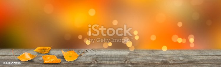 istock wooden table in front of abstract background 1003655594