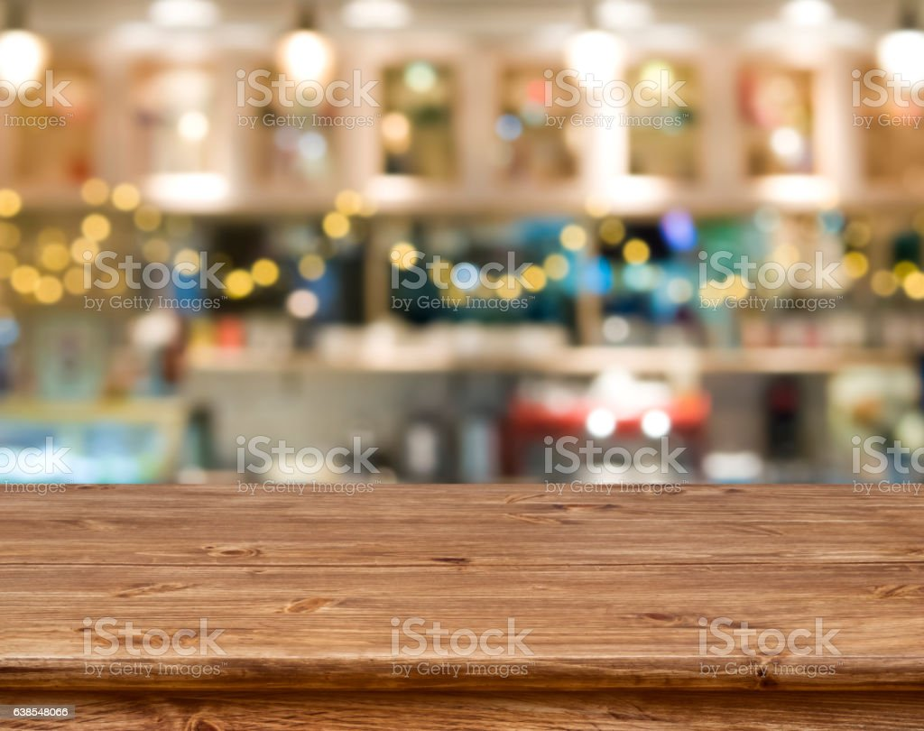 Wooden table in front of abstract blurred kitchen bench background stock photo
