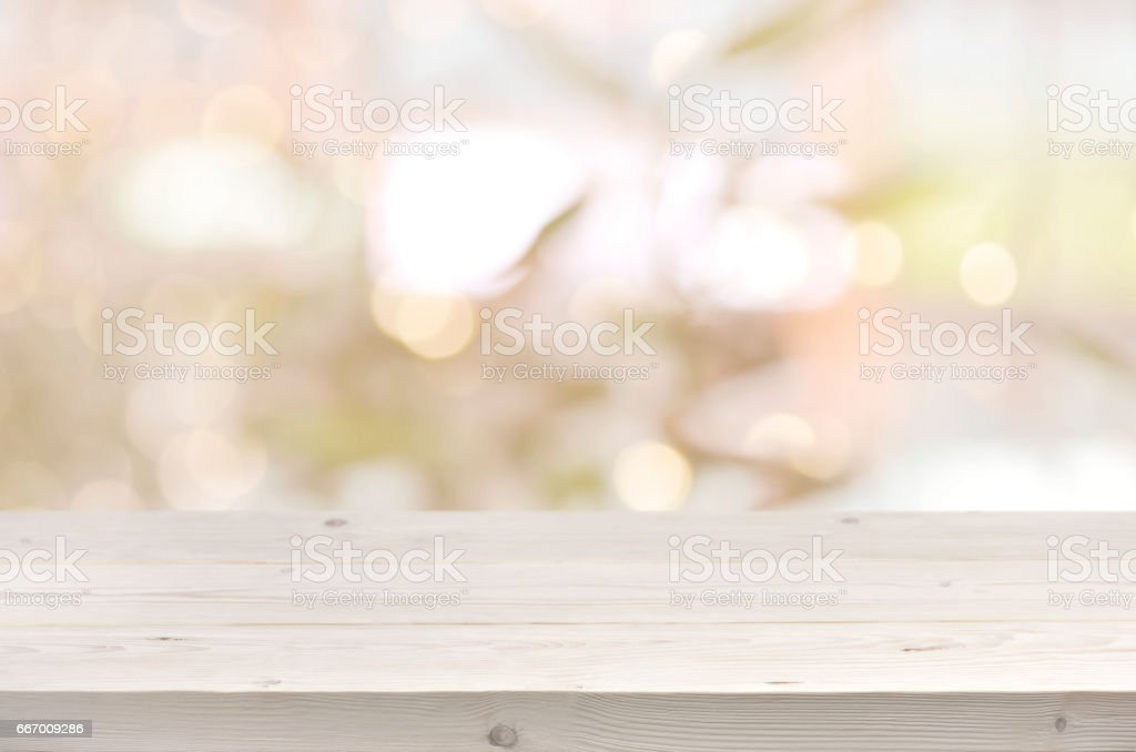 Wooden table in front of abstract blurred summer lights background stock photo