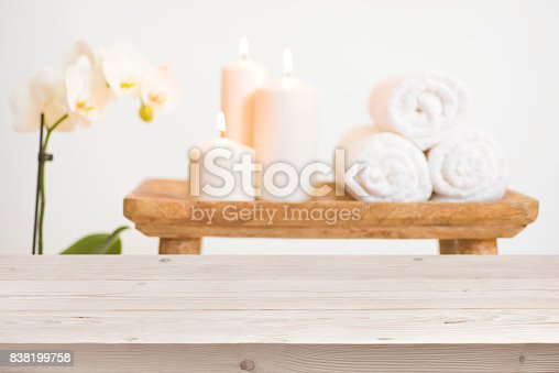 istock Wooden table in front of blurred background of spa products 838199758